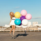 Happy young woman with colorful latex balloons Royalty Free Stock Photos