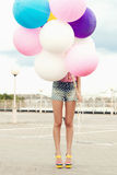 Happy young woman with colorful latex balloons Royalty Free Stock Photography