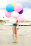 Happy young woman with colorful latex balloons Stock Image