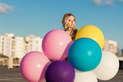 Happy young woman with colorful latex balloons Stock Photography