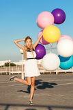 Happy young woman with colorful latex balloons Stock Photos