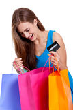 Happy young woman with colorful shopping bags visa isolated Royalty Free Stock Photo
