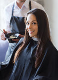 Happy young woman coloring hair at salon Stock Images