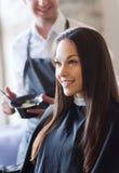 Happy young woman coloring hair at salon Royalty Free Stock Photos