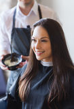 Happy young woman coloring hair at salon Royalty Free Stock Image