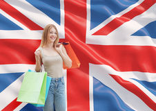 A happy young woman with the colourful shopping bags from the fancy shops. Great Britain flag background Stock Photography