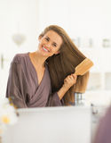 Happy young woman combing hair in bathroom Stock Photography