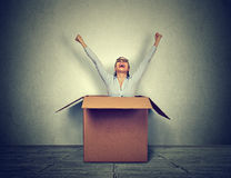 Happy young woman coming out from a small box. Happy woman coming out from a small box royalty free stock images