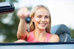 Happy young woman with convertible car key Royalty Free Stock Photography