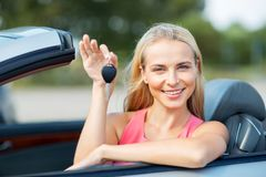 Happy young woman with convertible car key Stock Photography