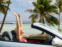 Happy young woman in convertible car over beach. Travel, summer holidays, road trip and people concept - happy young woman in convertible car enjoying sun over stock photos