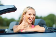Happy young woman in convertible car thumbs up Royalty Free Stock Photos