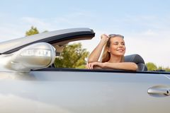 Happy young woman in convertible car stock image
