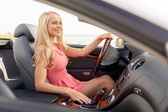 Happy young woman in convertible car royalty free stock photography