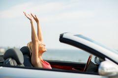 Happy young woman in convertible car. Travel, summer holidays, road trip and people concept - happy young woman in convertible car enjoying sun stock photography