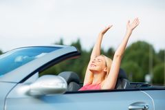 Happy young woman in convertible car Stock Photos
