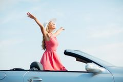 Happy young woman in convertible car. Travel, summer holidays, road trip and people concept - happy young woman wearing hat in convertible car enjoying sun royalty free stock photo