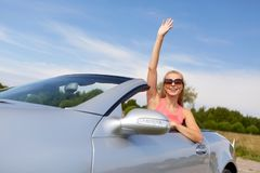 Happy young woman in convertible car. Travel, summer holidays, road trip and people concept - happy young woman wearing sunglasses in convertible car enjoying royalty free stock images