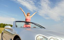 Happy young woman in convertible car. Travel, summer holidays, road trip and people concept - happy young woman wearing sunglasses in convertible car enjoying royalty free stock image