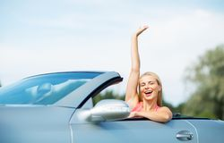 Happy young woman in convertible car waving hand Royalty Free Stock Photos