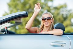 Happy young woman in convertible car waving hand Royalty Free Stock Photo