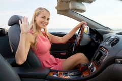 Happy young woman in convertible car waving hand Stock Photo