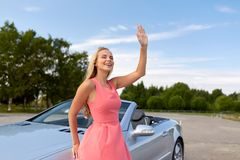 Happy young woman in convertible car waving hand Stock Images