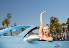 Happy young woman in convertible car waving hand Stock Photography