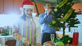 Happy young woman cooking salad for christmas dinner, man hug and helping