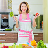 Happy young woman cooking a salad. Royalty Free Stock Photo