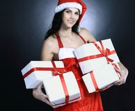 Happy young woman in costume of Santa Claus with lots of Christ. Mas shopping.  on black Royalty Free Stock Image