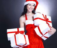 Happy young woman in costume of Santa Claus with lots of Christ. Mas shopping.  on black Stock Photo