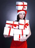 Happy young woman in costume of Santa Claus with lots of Christ. Mas shopping. isolated on black Royalty Free Stock Photo