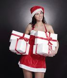 Happy young woman in costume of Santa Claus with lots of Christ. Mas shopping.  on black Royalty Free Stock Photo