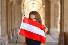 Happy young woman covering her face with austrian flag Stock Photography