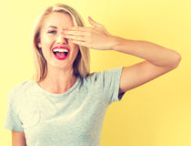 Happy young woman covering one eye with her hand Royalty Free Stock Photo