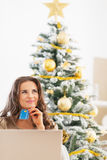 Happy young woman with credit card and laptop near christmas tree Royalty Free Stock Photo