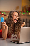 Happy young woman with credit card and laptop rejoicing Royalty Free Stock Photography