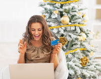 Happy young woman with credit card and laptop rejoicing Stock Photo