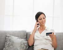 Happy young woman with credit card sitting on sofa Stock Image
