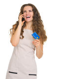 Happy woman with credit card talking mobile phone Stock Image