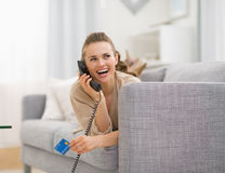 Happy young woman with credit card talking phone Royalty Free Stock Photo