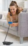 Happy young woman with credit card talking phone Stock Images