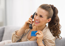 Happy young woman with credit card talking phone Royalty Free Stock Images