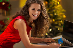 Happy young woman with credit card using laptop Royalty Free Stock Photo