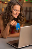 Happy young woman with credit card using laptop Stock Photos