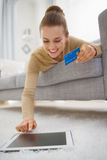 Happy young woman with credit card using tablet pc Royalty Free Stock Photos