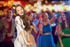 Happy young woman in crown at night club party. People, holidays, nightlife and celebration concept - happy young women or teen girl in party dress and princess Royalty Free Stock Image