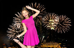 Happy young woman in crown over firework at night. People, holidays, party and fashion concept - happy young woman or teen girl in pink dress and princess crown Royalty Free Stock Photos