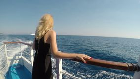 Happy young woman on cruise ship vacation traveling on sea smiling and admiring the waves -. Happy young woman on cruise ship vacation traveling on sea smiling stock footage